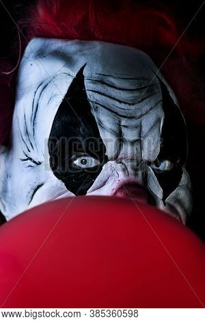 closeup of a scary evil clown with red hair and white eyes, staring at the observer, with a red balloon in front of him, against a black background