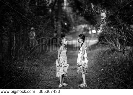 Two little girlfriends in the pine Park. Black and white photography.