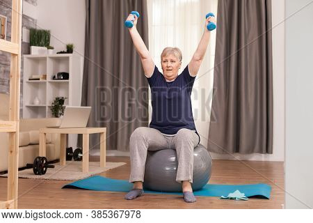 Grandmother With Healthy Lifestyle Practicing Fitness At Home. Old Person Pensioner Online Internet