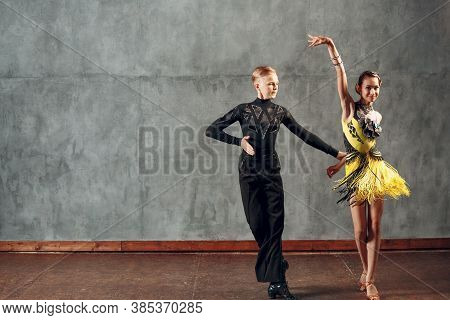 Young Couple Sport Dancers Dancing In Ballroom Dance Cha-cha-cha.
