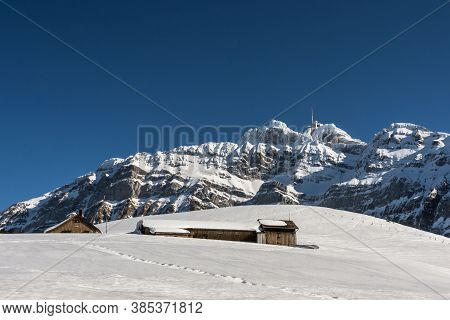 Small mountain huts on an alp in front of the Saentis massif in winter, Canton Appenzell-Ausserrhoden, Switzerland