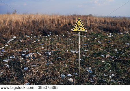 Yellow Triangle With Biohazard Symbol Warning On Abandoned Territory With Trash. Garbage Waste Field
