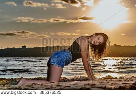 A Young Brunette Woman In A Black Undershirt And Denim Shorts Resting On The Sandy Seashore. Summer