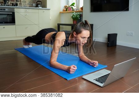 A Serious Sporty Girl In A Black Workout Tight Suit Is Doing Plank Watching An Online Video On A Lap