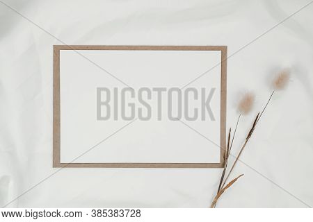 Blank White Paper On Brown Paper Envelope With Rabbit Tail Dry Flower On White Cloth. Mock-up Of Hor