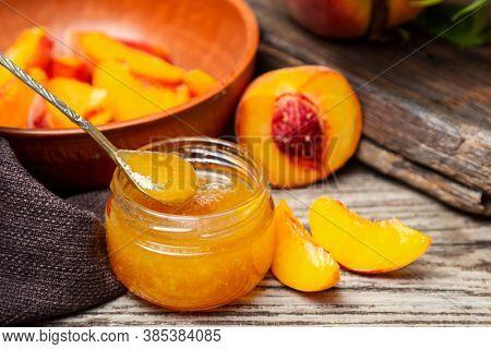 Peach Jam In Glass Jar With Peach Wedges And Whole Peach Fruit. Peach Jam On Wooden Table