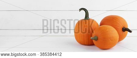 Three small pumpkins on white wooden background