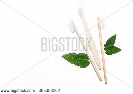 Bamboo Toothbrush And Green Leaves On An Isolated Background. Tooth Cleaning. Article About Choosing