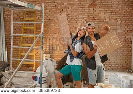 Happy young loving couple building a new home.