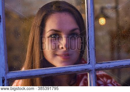 Portrait of pretty woman in warm room indoor at home in winter night. Shot from outdoor trough the window.