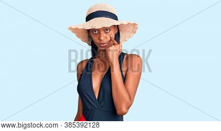 Young african american woman wearing swimsuit and summer hat pointing to the eye watching you gesture, suspicious expression