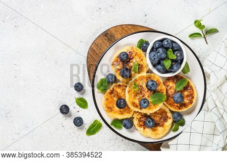 Cottage Cheese Pancakes, Syrniki With Blueberry In Craft Plate. Top View On White Stone Table.