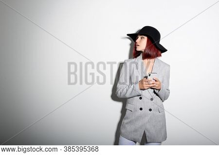 Young stylish woman wearing grey jaket and black hat using smartphone indoor