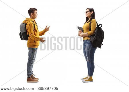 Full length profile shot of a teenager talking to an older female student isolated on white background