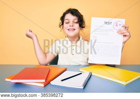 Cute hispanic child showing a passed exam sitting on the desk screaming proud, celebrating victory and success very excited with raised arm