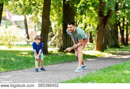 family, fatherhood and people concept - happy father with little son compete in running at summer park