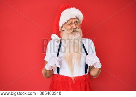 Old senior man wearing santa claus costume with suspenders winking looking at the camera with sexy expression, cheerful and happy face.