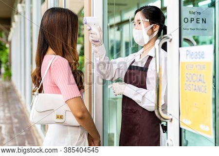 Asian waitress with face mask taking temperature to female customer woman before getting in restaurant. New normal restaurant concept after coronavirus covid-19 pandemic.