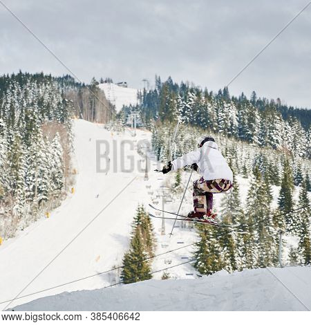 Male Skier In Winter Jacket And Helmet Skiing Downhill In Snowy Mountains With Beautiful Snowy Trees