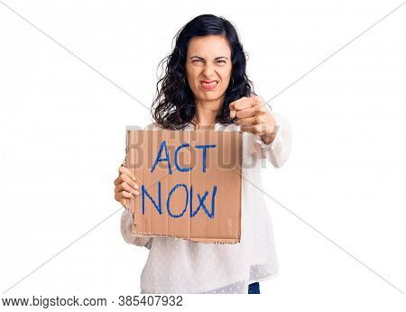 Young beautiful hispanic woman holding act now banner annoyed and frustrated shouting with anger, yelling crazy with anger and hand raised