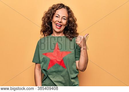 Middle age beautiful woman wearing t-shirt with red star revolutionary symbol of communism pointing thumb up to the side smiling happy with open mouth