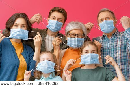 Family is wearing facemasks during coronavirus and flu outbreak. Virus and illness protection, quarantine. COVID-2019. Taking on or taking off masks. People on pink wall background.