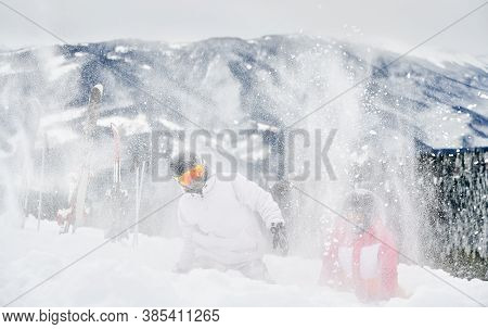 Two Skiers In Ski Suits And Helmets Throwing Fresh Powder Snow High In The Air. Man And Woman In Ski