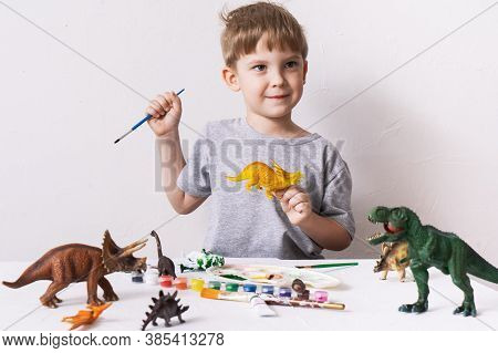 Hobby: A Boy, A Preschooler, Paints With A Brush And A Tassel A Small Figure Of A Dinosaur Toy.