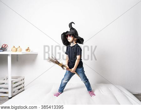 A Little Boy In A Black Witch Hat And Pink Glasses Holds A Broom.