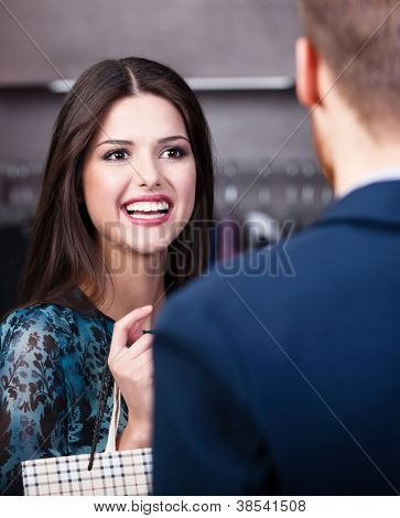Smiling girl with long dark hair talks to shop assistant