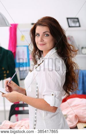 Portrait Of Cheerful Fashion Designer Looking At Camera With Happiness. Seamstress Making Notes In T
