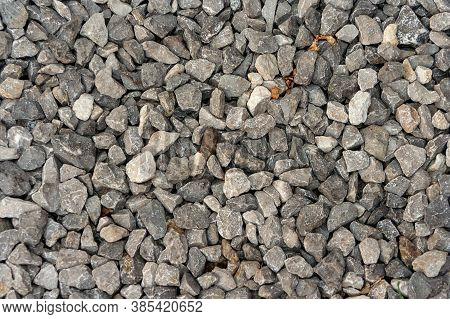Small Road Stone Background, Dark Gravel Pebbles Stone Texture. Closeup Top View Gravel. Gravel In G