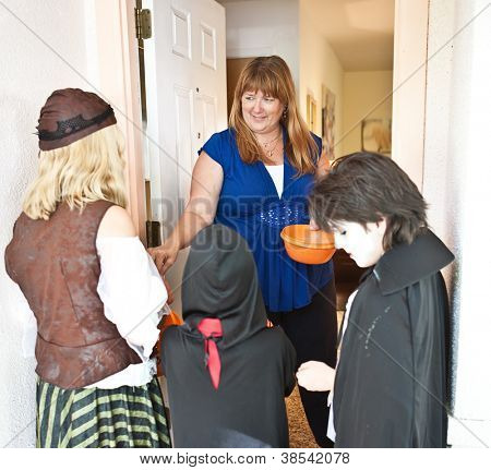 Nice woman passing out Halloween candy to trick or treaters at her door.
