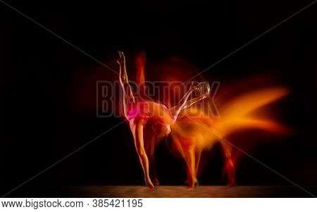Fireball. Young Flexible Girl Isolated On Black Studio Background In Mixed Light. Female Rhythmic Gy