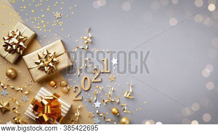 Golden Gift Or Present Boxes With Golden Bows, 2021 Number And Confetti Top View. Christmas And New
