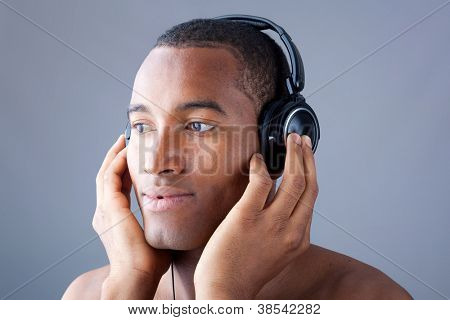 Jonge zwarte man, luisteren naar muziek met een koptelefoon over grijze achtergrond