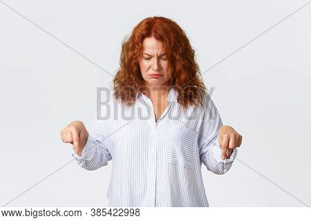 Skeptical And Displeased Middle-aged Redhead Woman Complaining, Smirk And Looking Doubtful, Pointing