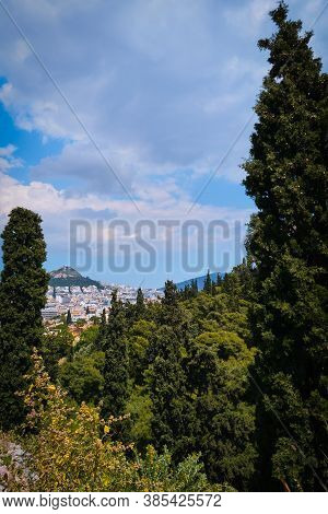 View Of Lycabettus Hill From Areopagus Hill, Rich Foliage, High Cedar Or Cypress Trees. Athens, Gree