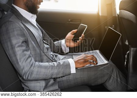 Unrecognizable Black Businessman Using Smartphone And Laptop In Car On A Way To Office. African Amer