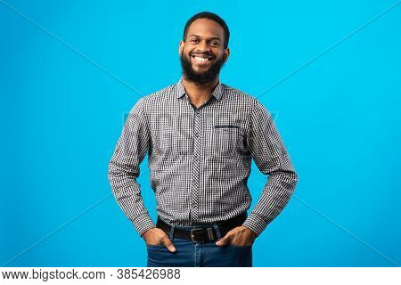 Portrait Of Handsome Young Black Man Standing Isolated On Blue Studio Background Looking At Camera.