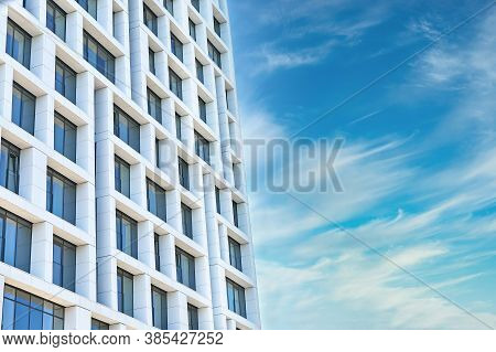 Exterior Of Modern Multistory Building Against Cloudy Sky