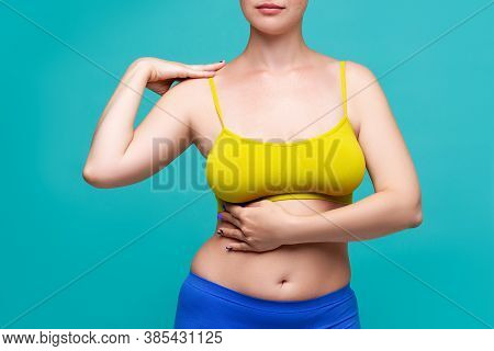 Woman In Yellow Top Bra With Big Natural Breasts On Blue Background