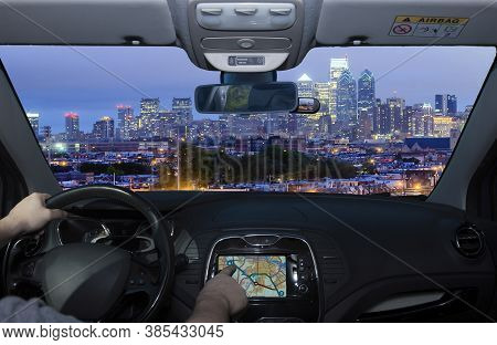 Driving A Car While Using The Touch Screen Of A Gps Navigation System Towards Philadelphia Skyline A