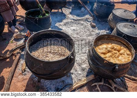 African cooking outdoors, huge pots of porridge pap samp and spinach in a few cast iron pots