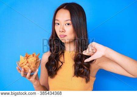 Young beautiful chinese girl holding nachos potato chips with angry face, negative sign showing dislike with thumbs down, rejection concept