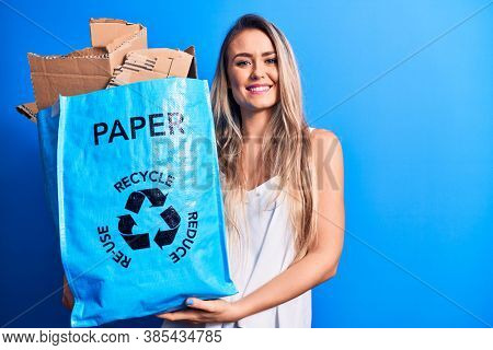 Young beautiful blonde woman recycling holding paper recycle bag full of paperboard looking positive and happy standing and smiling with a confident smile showing teeth