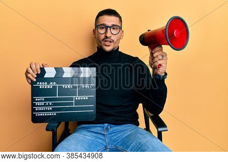 Handsome man with tattoos holding video film clapboard and megaphone in shock face, looking skeptical and sarcastic, surprised with open mouth