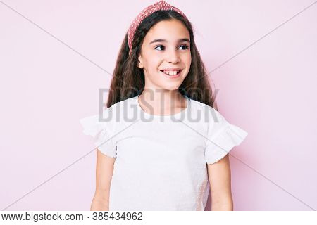 Cute hispanic child girl wearing casual clothes and diadem looking away to side with smile on face, natural expression. laughing confident.