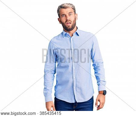 Young handsome blond man wearing elegant shirt in shock face, looking skeptical and sarcastic, surprised with open mouth