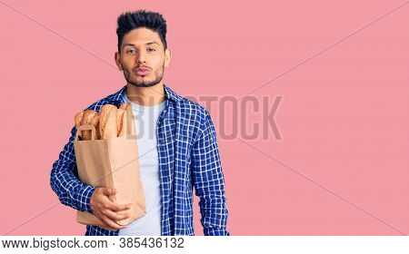 Handsome latin american young man holding paper bag with bread looking at the camera blowing a kiss on air being lovely. love expression.